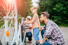 Senior Man Helping His Son And Grandson Fixing Upside Down Bike Outdoor In City Park In Summer Day. Family Relation Different Generation Concept.
