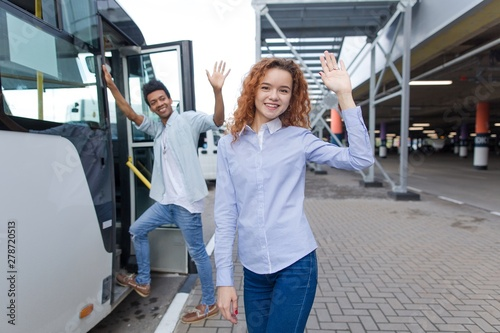 Photo Red-haired girl with an African guy standing at the bus stop get on the bus to s