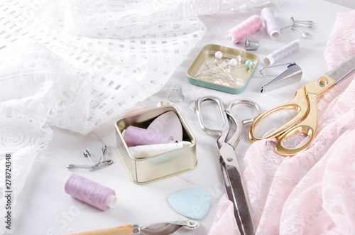 Fotomural  Boxes with thread, pins, golden and silver scissors, elegant fabric on the white table