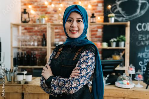 Fotomural  asian muslim girl wearing hijab working as waitress in cafe bar