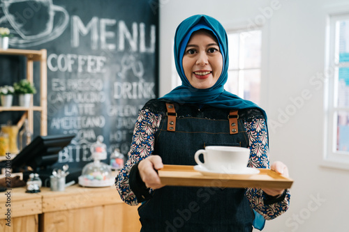 Cuadros en Lienzo  young muslim employee barista woman standing holding cup of tea on plate at coffee shop counter