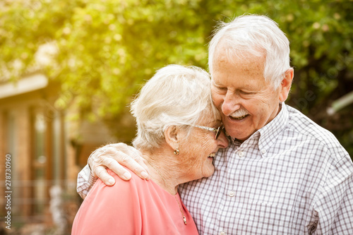 Fotografía  older couple are standing in the garden, hugging each other and laughing at each