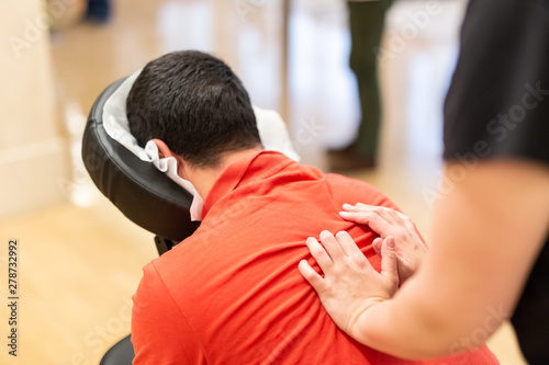 Man receiving shiatsu on a quick massage chair