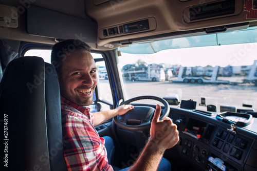 Obraz Portrait of truck driver sitting in his truck holding thumbs up. Transportation and trucking services. - fototapety do salonu