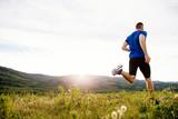 back man runner running on summer plateau motley grass in sunset