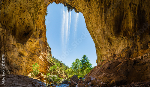 Poster Rivière de la forêt Inside Tonto Natural Bridge in the mountains of Arizona looking out from behind a waterfall.