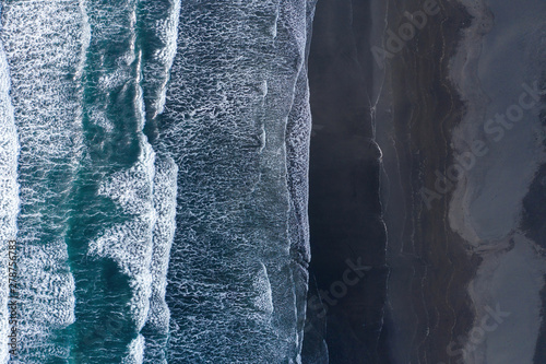 Canvastavla Aerial view of Atlantic ocean waves washing black sandy beach