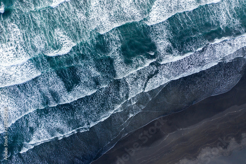 Платно Aerial view of Atlantic ocean waves washing black sandy beach