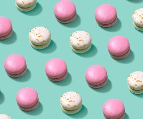 Colorful cake macaron or macaroon on turquoise pastel background from above.