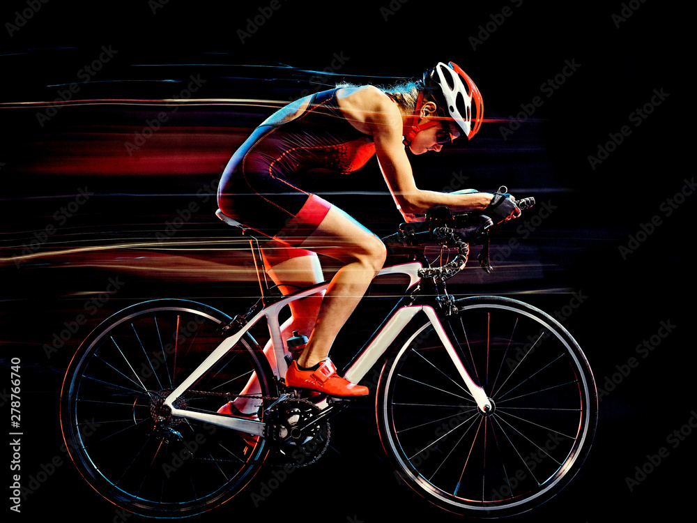 Fototapeta one caucasian woman triathlon triathlete cyclist cycling studio shot isolated on black background with light painting effect