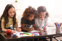 Schoolgirls Drawing With Colorful Pencils At Home