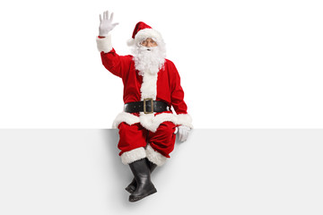 Santa claus sitting on a panel and waving