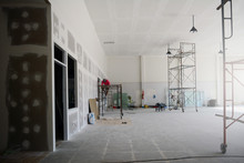 The Iron Scaffoldings On Tile Ground And The Black Lamp On  The Ceiling With The Labor While  Renovation  The Old Office