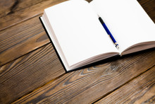 Ballpoint Pen In Open Notebook On A Dark Brown Wooden Background. Blank Pages In Notebook. Concept - Daily Writing