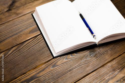 Fotomural  Ballpoint pen in open notebook on a dark brown wooden background