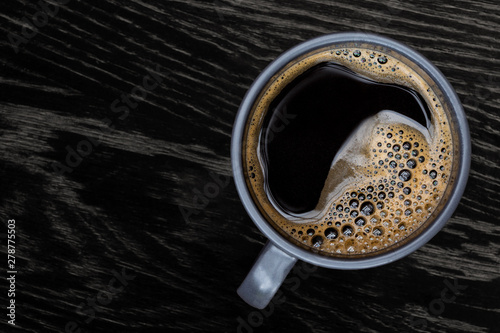 Black coffee in a blue-grey ceramic mug isolated on dark brown wood table with grain from above. Space for text.