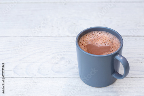 Foto op Plexiglas Chocolade Hot chocolate in a blue-grey ceramic mug isolated on white painted wood. Space for text.