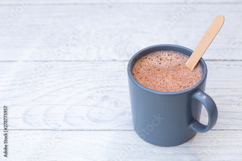 Cafe Hot chocolate in a blue-grey ceramic mug with wooden stirrer isolated on white painted wood. Space for text.