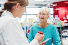 Senior Woman In Pharmacy Talki...