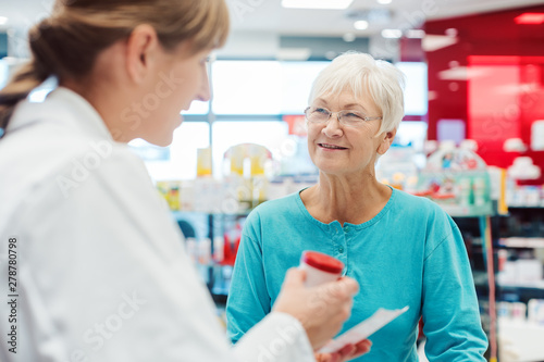 Papiers peints Pharmacie Senior woman in pharmacy talking to the chemist or pharmacist