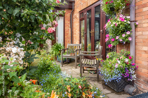 Foto op Aluminium Tuin A pair of wooden chairs in a corner of a garden