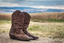 Cowboy Boot In Rural Scene With Moody Sky