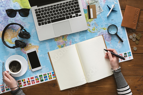 Woman drinking coffee and planning her trip in the office