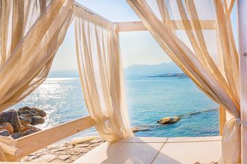 Fototapeta na wymiar Sea view through the curtains of a luxurious bed on the beach