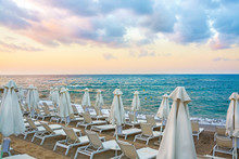 Sun Beds And Umbrellas On An Empty Beach In The Background Of A Beautiful Cloudy Sky In Crete Island, Greece. Concept Of Summer Holiday, Vacation And Tourism.
