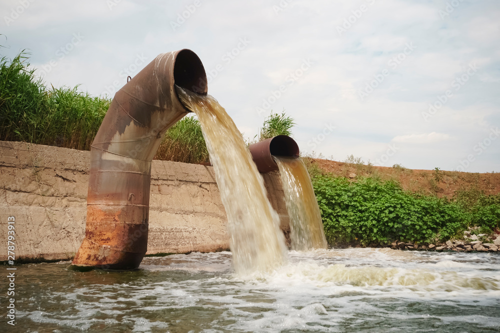 Fototapeta Wastewater from two large rusty pipes merge into the river in clouds of steam