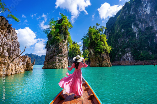 Fototapeta Beautiful girl standing on the boat and looking to mountains in Ratchaprapha Dam at Khao Sok National Park, Surat Thani Province, Thailand. obraz na płótnie