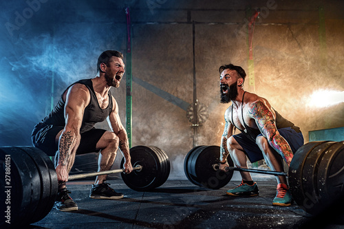 Autocollant pour porte Fitness Two muscular bearded tattoed athletes training, lifting heavy weight bar in smoke at gym. Scream. Working hard. Exercise for the muscles of the back