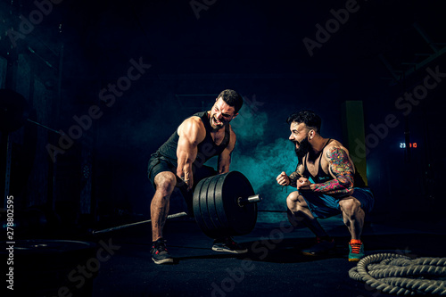 Two muscular bearded tattoed athletes training, one lift heavy weight bar when other is motivating Poster Mural XXL