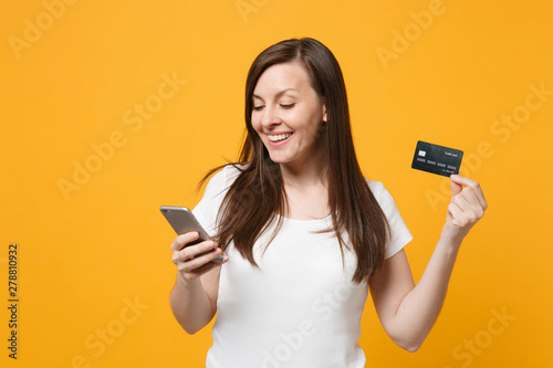 Fototapeta Portrait of smiling young woman in white casual clothes using mobile phone, holding credit bank card isolated on yellow orange wall background in studio. People lifestyle concept. Mock up copy space. obraz na płótnie