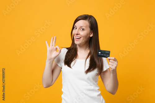 Fototapeta Portrait of pretty young woman in white casual clothes showing OK gesture, holding credit bank card isolated on yellow orange wall background in studio. People lifestyle concept. Mock up copy space. obraz na płótnie