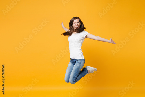 Portrait of funny screaming cheerful young woman in casual clothes jumping, spreading hand wall isolated on bright yellow orange background in studio Wallpaper Mural