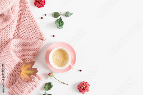 Staande foto Thee Autumn cozy composition. Dry yellow leaves, flowers, cup of coffee, pink knitted sweater on white background. Fall concept. Autumn background. Flat lay, top view, copy space