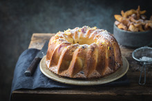 Rustic Style Apple Bundt Cake Sprinkled With Icing Sugar On Old Wooden Table