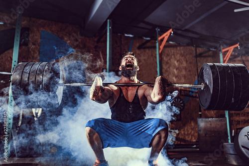 Fényképezés  Muscular bearded tattoed fitness man doing deadlift a barbell over his head in modern fitness center
