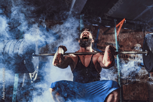 Fotografiet  Muscular bearded tattoed fitness man doing deadlift a barbell over his head in modern fitness center