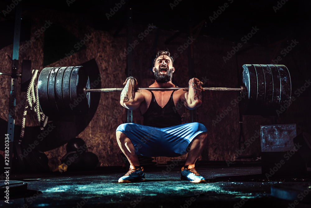 Fototapeta Muscular bearded tattoed fitness man doing deadlift a barbell over his head in modern fitness center. Functional training. Snatch exercise