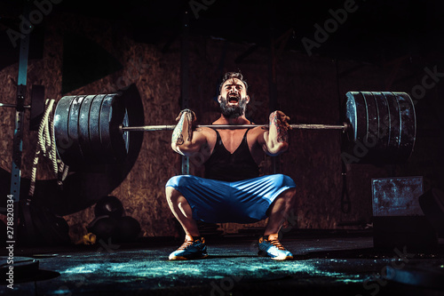Valokuva  Muscular bearded tattoed fitness man doing deadlift a barbell over his head in modern fitness center