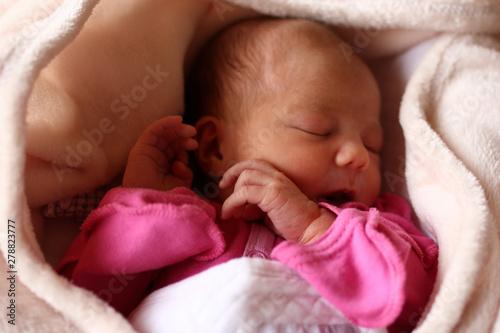Photo Cute sleeping newborn baby in pink baud on her bed under beige blanket