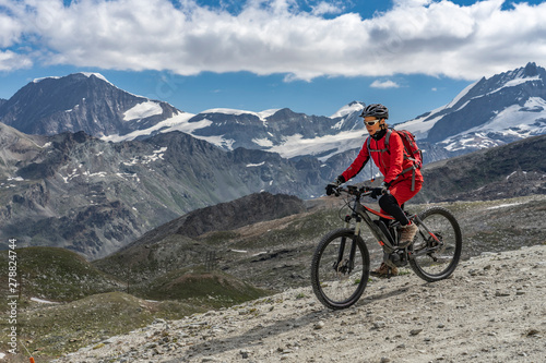 Photo  active senior woman, riding her electric mountainbike below the famous Gornergra