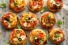 Mini Vegetarian Pizzas With The Addition Various Kinds Of Vegetables , Mozzarella Cheese And Fresh Basil On A On White Baking Paper, Close-up, Top View.
