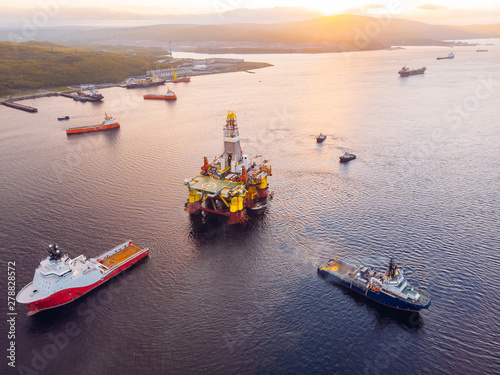 Ships are transporting offshore oil rig for installation sea for repairs, aerial top view