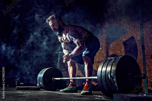 Fényképezés  Muscular fitness man preparing to deadlift a barbell over his head in modern fitness center