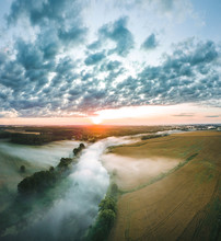 Aerial View Over A Misty Morning Over Countryside. Fog Covering The Crop Fields And River. Colorful Sunrise Over The Fields And Forest.