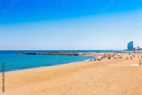 Foto auf AluDibond Barcelona Barceloneta beach in Barcelona. Nice sand beach with palms. Sunny bright day with blue sky. Famous tourist destination in Catalonia, Spain