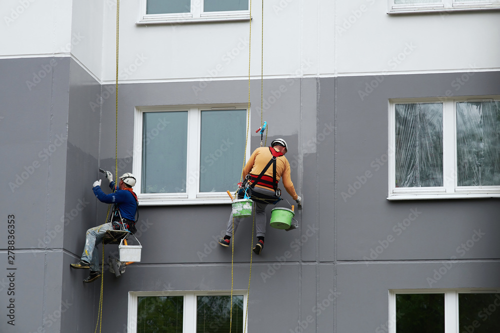 Fototapeta Worker hanging on rope and paints building wall with roller. Painter hanging on cable with paint buckets, industrial climber repairing house facade. Industrial alpinist and climbing. Rigging equipment